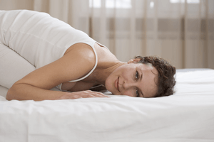 a woman laying down on her mattress pressing her face against it to feel the texture and comfort