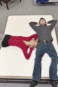 a couple laying on a mattress