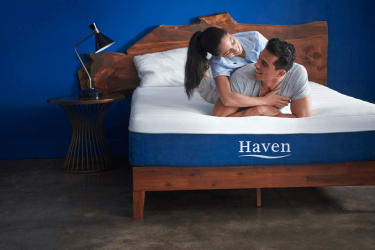 a couple laying on top of a Haven mattress