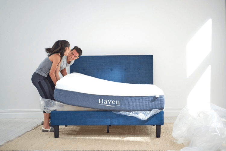 a couple placing a mattress on a bed